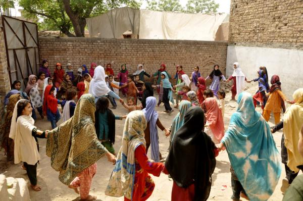 Girls displaced from their homes by conflict in north-western Pakistan dance with local children at Save the Children's temporary learning space in Peshawar District, Pakistan. Save the Children