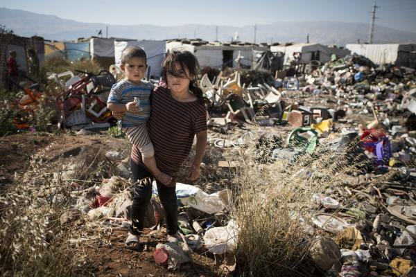 Jamila*, eight, with her brother Adib*, two, at a tented refugee settlement in Lebanon, near the Syrian border. *Names have been changed to protect identities. Photo Jonathan Hyams/Save the Children.