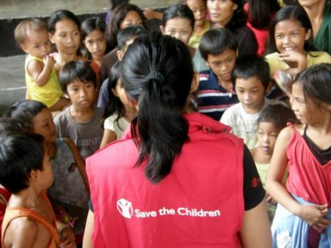 A Save the Children staff member talks to children in the evacuation centre in Pateros, the Philippines, to find out more about their living conditions and needs after recent flooding. Children require clean water, electricity, latrines, a safe place to play and access to health services. Save the Children